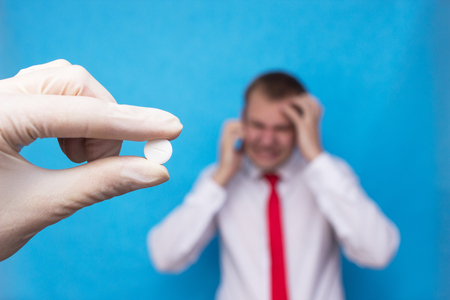 The doctor holds a pill against the background of a man who has side effects on medications, medical, corticosteroids