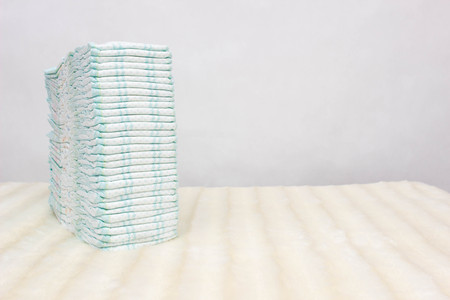 A stack of baby diapers on a white background, protection against leakage, dryness and comfort, hypoallergenic, copy space, hygienics Banco de Imagens