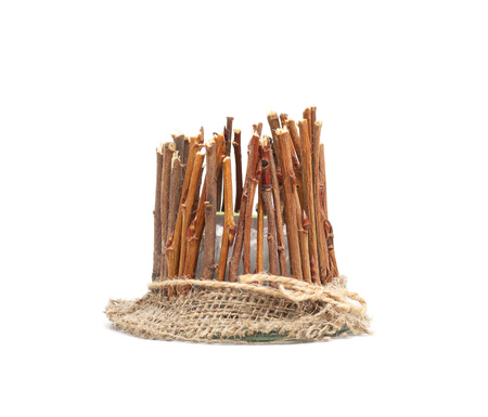 Decorative candlestick made of burlap and twigs on a white background, isolate, illuminated Banco de Imagens