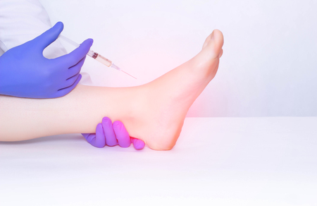 The doctor makes an injection into the ankle joint of the patient in plasma therapy to eliminate inflammation and pain, relieve edema, copy space, osteoarthritis Standard-Bild - 121938407