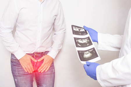A patient with chronic prostatitis and problems with libido at the reception and consultation with a urologist doctor who is holding ultrasound diagnostic images, medical, x-ray pictures Banco de Imagens