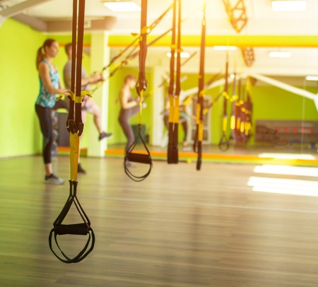 Lesson and exercise in a modern gym with loops, copy space, sun, excess weight
