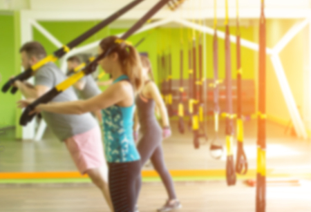 People in the gym are engaged on the loops and perform an extension exercise on the triceps, muscle strengthening, blurred, sunset, excess weight
