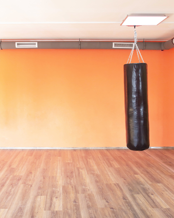 Boxing modern punching bag on the background of the orange wall in the new modern gym, copy space, power Banco de Imagens