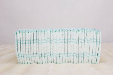 A stack of baby diapers on a white background, protection against leakage and comfort, copy space