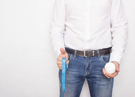 A man on a white background holds a centimeter tape and cream on the background of the penis, the concept of increasing the member with the help of ointments and creams, copy space,