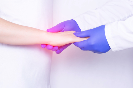 Doctor examines a girl's wrist joint for sprain, inflammation and pain in her wrist, close-up, arthrosis, chronic pain Stockfoto