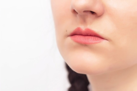 Face of a beautiful girl on a white background and red lips, the concept of lip augmentation in plastic surgery and aesthetic cosmetology, copy space, contour plastic