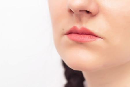 Visage d'une belle fille sur fond blanc et lèvres rouges, concept d'augmentation des lèvres en chirurgie plastique et cosmétologie esthétique, espace de copie, contour plastique