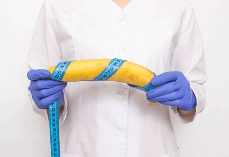 Doctor holds banana in hand with measuring tape. Concept of increasing male penis and operation, sexual intercourse