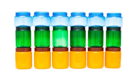 Multicolored plastic jars of orange, green and blue on a white background, high density polyethylene Stock Photo