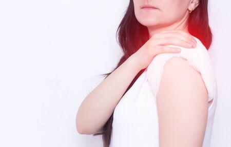 Das Mädchen hält sich an der wunden Schulter fest, die eine heilende Kompresse, weißen Hintergrund, Kopierraum, Medizin, Polymyalgie hat Standard-Bild
