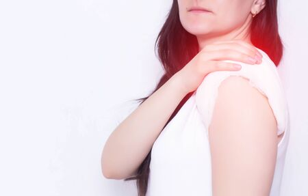 The girl holds on to the sore shoulder which has a healing compress, white background, copy space, medical, polymyalgia 写真素材