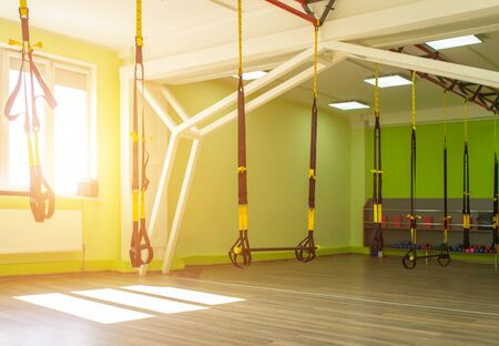 Modern new gym in the fitness center to practice a new sport of the TRX loop, sunset