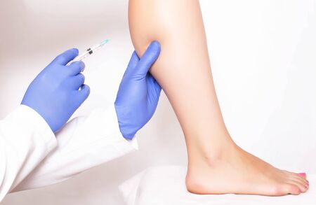 Doctor cosmetologist makes rejuvenation beauty injection to the calf muscle on the leg of the girl. Rejuvenation with injections of Hilauri acid