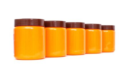 Orange plastic jars with a brown lid on a white background, isolate
