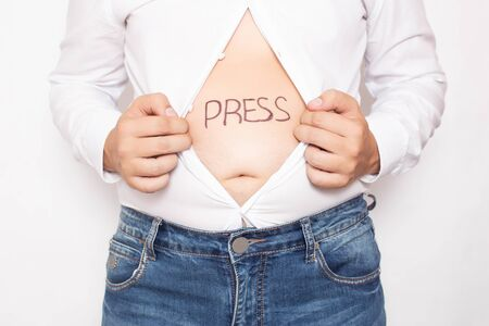 A man holds a shirt open with a bare stomach on which the word press is written, obesity concept and sports, fatty