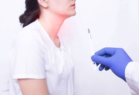 Doctor holding a surgical scalpel on the background of a girl with throat disease, concept of removing adenoids by surgery, surgery for throat diseases, medical