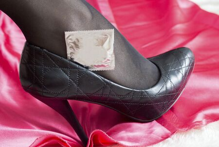 Womans leg in black sexy pantyhose and a condom in shoes concept of safe sex and sexually transmitted infections AIDS and HIV, close-up