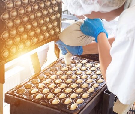 female confectioner fixes dough in the baking form of nuts with condensed milk. Confectionery production, handmade, food Reklamní fotografie