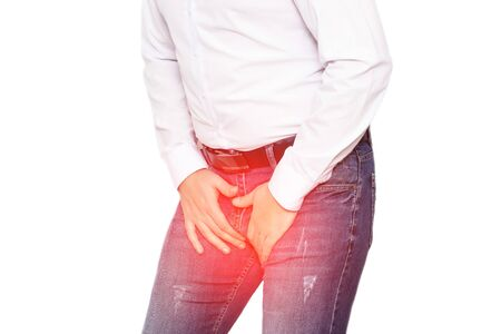 A man in a white shirt holds on to his groin, the concept of pain and inflammation in the groin, genital infections in men and prostatitis. White background, isolate, chronic Stock Photo