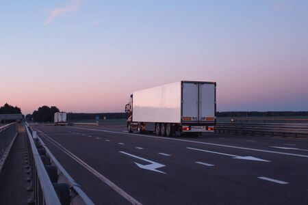 A convoy of trucks trucks transports the cargo in the evening on the highway, the concept of logistics and freight, copy space, trucking industry Reklamní fotografie