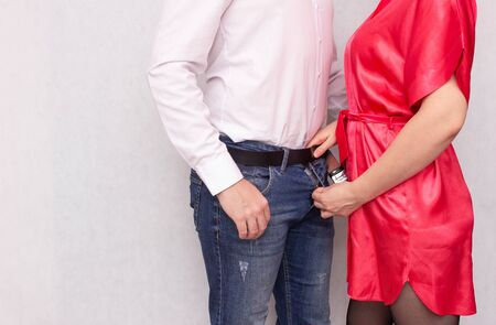 Girl flattens male partner to his fly the concept of impotence and male sexual health in men, white background, copy space