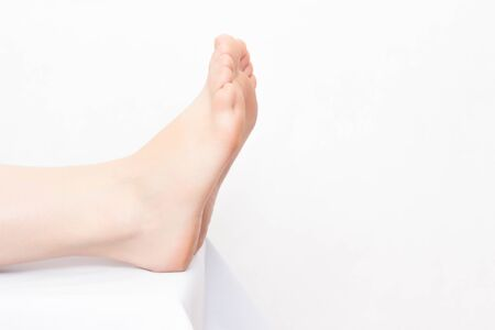 Female legs on white background, concept of unpleasant foot odor and fungal diseases, copy space, depilation