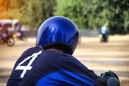 Motorcyclist in a helmet on the background of motorcycle racing competitions, copy space, motocross