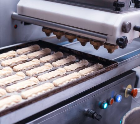 Automatic line for the production of eclairs. Eclair Cake Dough Baking, traditional