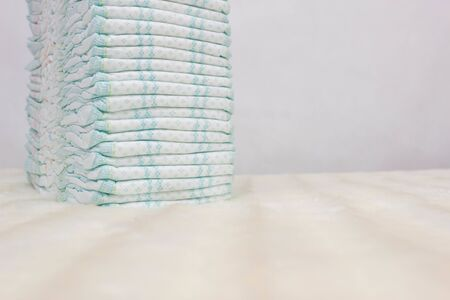 Pile of baby diapers on a white background, protection against leakage, dryness and comfort, hygiene