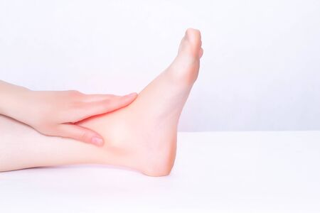 The girl holds on to the sore ankle joint in which the inflammation tends and stretches the ligamentous apparatus, medical, white background, copy space, osteoarthritis Reklamní fotografie