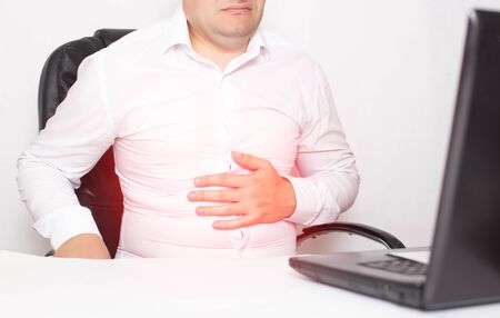 Male office worker holding stomach stomach, gastritis and stomach ulcer, Helicobacter pylori, esophageal diverticulums