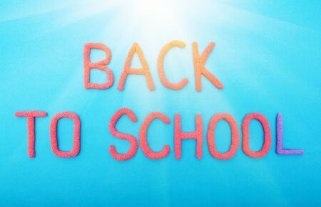 The inscription back to school on a blue background backlit by the sun, concept of kids going to school
