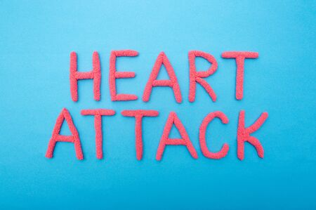 Inscription Heart attack on a blue background concept of myocardial infarction and heart muscle, brain