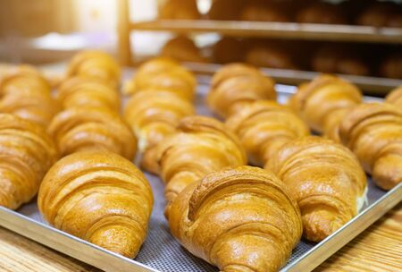 Fresh golden croissants with filling, background. Pastry confectionery