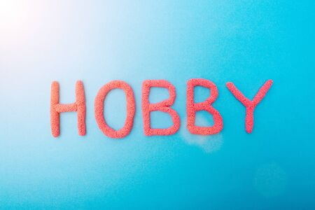 Red plasticine hobby lettering on blue background, hobbies concept
