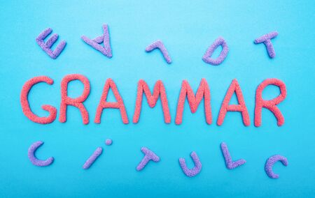 The word grammar on a blue background and letters scattered in a chaotic manner, the concept of literacy at school, inscription, education