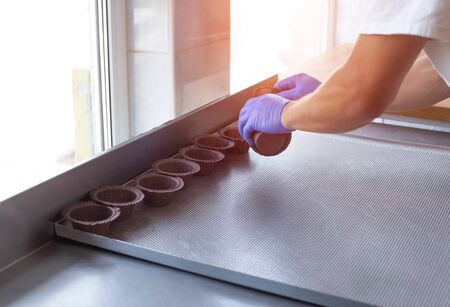 The worker is arranging cupcake and muffin molds on the table. Production of muffins in the confectionery industry. Copy space, bakery products