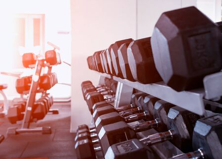 Modern black dumbbells in the gym against the background of the sun, copy space