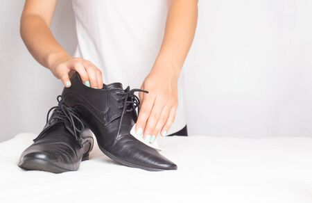 Girl wipes shoes with wet special shoe napkins, copy space, wet wipe 版權商用圖片