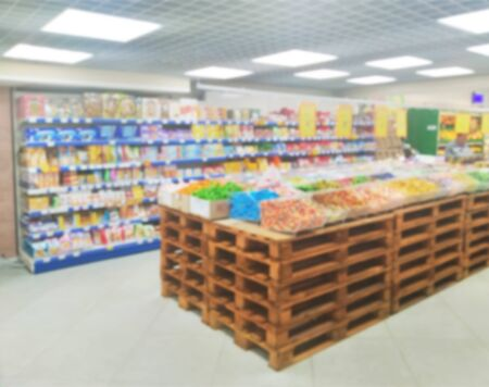 Supermarket inside with goods, pallets with goods and sweets, blurred, customer