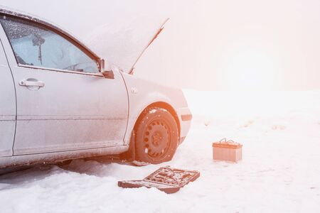 A car with a raised hood on a background of a snowy field, tools and a discharged car battery near the car, the concept of a car breakdown in winter, automotive