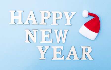 The inscription of the letters happy new year on a blue background. Little santa claus hat, new year holiday concept. Background