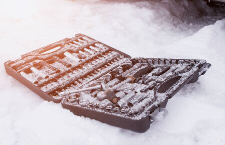 Snow-covered set of car tools in the snow. The concept of breakdowns and malfunctions of diesel and gasoline cars in the winter, poor-quality diesel fuel, problem engine start, instruments 版權商用圖片