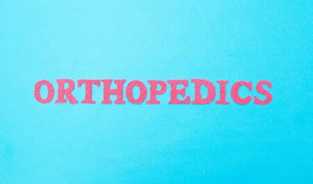 Orthopedics inscription in red letters on a blue background. The concept of the section of medicine and treatment of injuries of the joints and spine. Endoprosthetics and arthroscopy, musculoskeletal system.