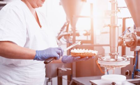 The pastry chef makes cake using modern equipment for the production of cakes. Line for spreading cream on biscuit cake. Industry, working 版權商用圖片