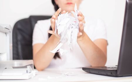 Caucasian girl office worker tears paper on the table. The concept of burnout and depression in the workplace, stress, chronic fatigue syndrome