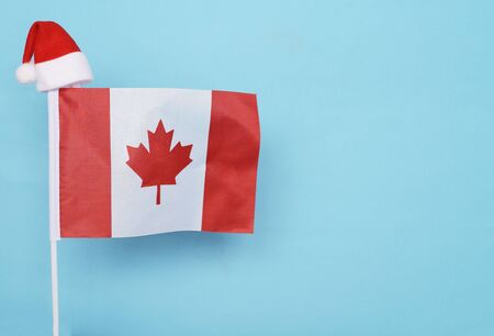 Flag of Canada with little santa claus hat on blue background. New Year winter holiday concept, copy space, beautiful