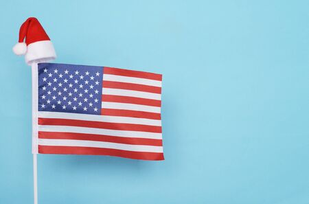 Flag of USA with little santa claus hat on blue background. New Year winter holiday concept, copy space, beautiful